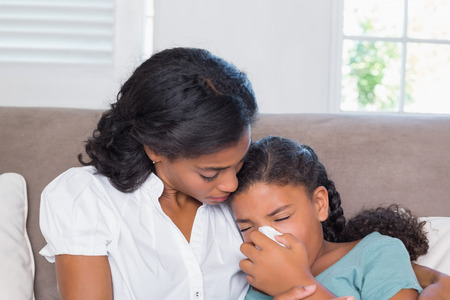 curly hair child: Concerned mother cuddling sick daughter at home in living room