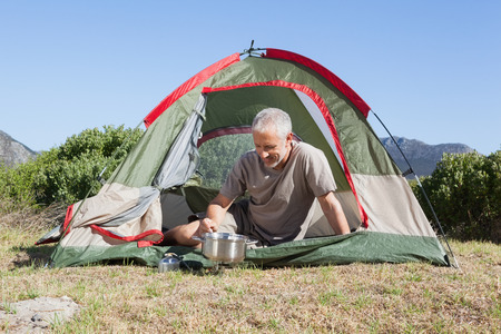 adventuring: Happy camper cooking on camping stove outside his tent on a sunny day