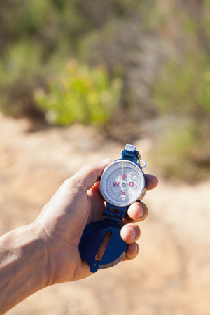 adventuring: Hiker holding his compass in the countryside on a sunny day Stock Photo