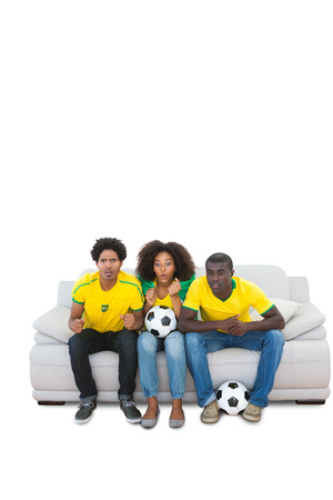 Nervous brazilian football fans in yellow on the sofa on white background photo
