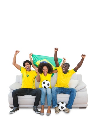 Cheering brazilian football fans in yellow on the sofa on white background photo