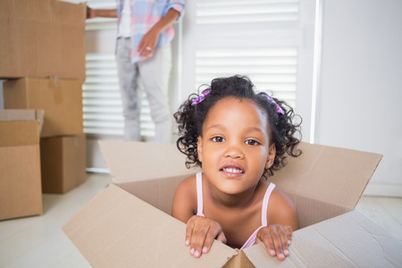 moving box: Cute daughter sitting in moving box in new home Stock Photo