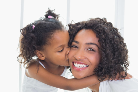 Pretty mother with her daughter kissing her cheek at home in the bathroom photo
