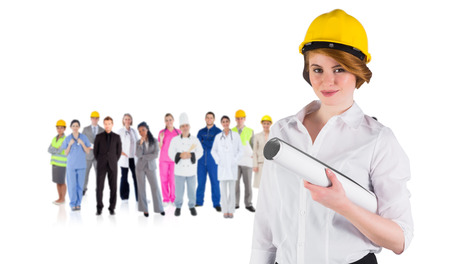 boiler suit: Composite image of pretty young architect smiling at camera against group of workers Stock Photo