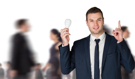Composite image of businessman holding light bulb and pointing against group of workers photo
