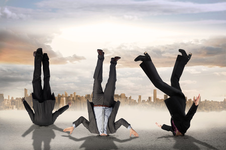 burying: Composite image of businessmen burying their heads against large city on the horizon