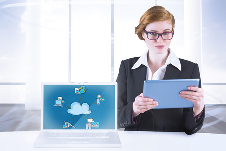 Redhead businesswoman using her tablet pc against bright room with columns photo