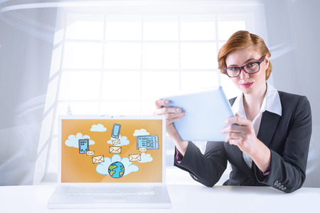 Redhead businesswoman using her tablet pc against room with large window showing city photo