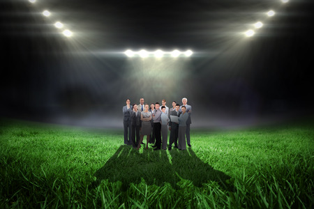 business pitch: Business team looking at camera against football pitch with bright lights Stock Photo