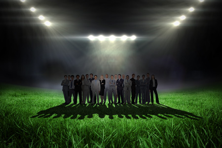 business pitch: Business people standing up against football pitch with bright lights