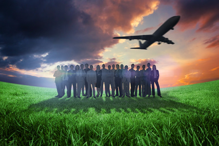 Business people standing up with airplane against green field under orange sky photo