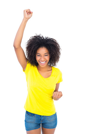 hot pants: Pretty girl in yellow tshirt and denim hot pants cheering at camera on white background Stock Photo