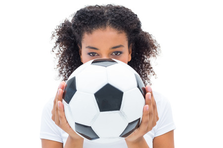Pretty football fan in white holding ball over face on white background Stock Photo