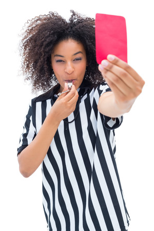 Pretty referee blowing her whistle and showing red card on white background photo