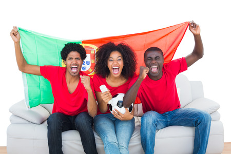 Cheering football fans in red sitting on couch with portugal flag on white background photo