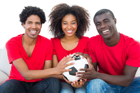 football fans: Happy football fans in red holding ball together on white background