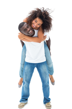 Casual man giving his smiling girlfriend a piggy back on white background photo