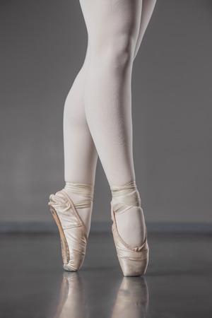 ballet slippers: Ballerina standing en pointe in ballet slippers in the ballet studio Stock Photo