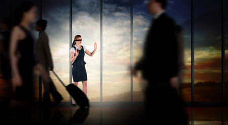 Redhead businesswoman in a blindfold against room with large window looking on landscape