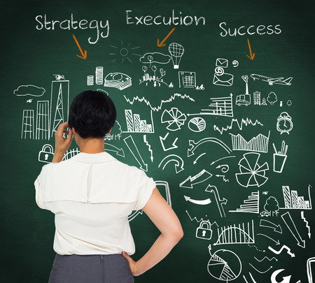 Thoughtful businesswoman against green chalkboard with business buzzwords photo