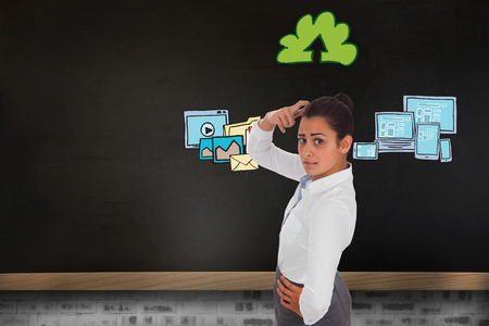 Worried businesswoman against blackboard on wall with business technology doodle photo