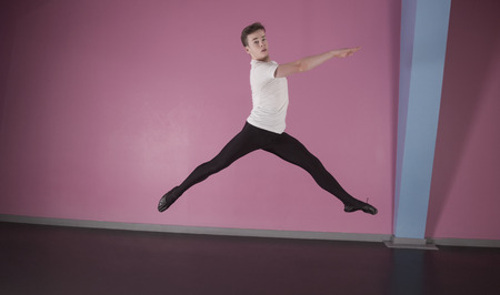 Focused male ballet dancer leaping  in the dance studio photo