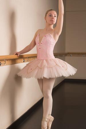 en pointe: Beautiful ballerina standing en pointe holding barre in the dance studio Stock Photo