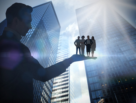 Composite image of businessman holding business team against low angle view of skyscrapers photo