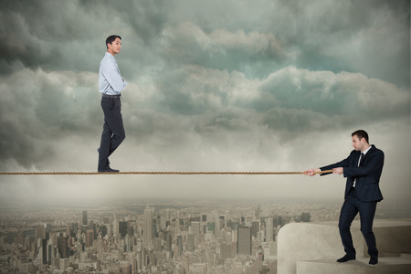 Young business man pulling a tightrope for businessman against balcony overlooking city photo
