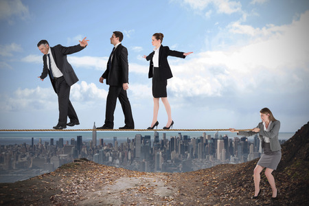Young businesswoman pulling a tightrope for business people against large city on the horizon Stock Photo