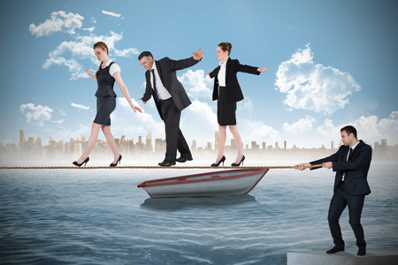tight focus: Young businessman pulling a tightrope for business people against small boat in the sea with city on horizon Stock Photo
