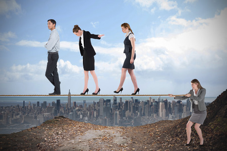 Young businesswoman pulling a tightrope for business people against large city on the horizon photo
