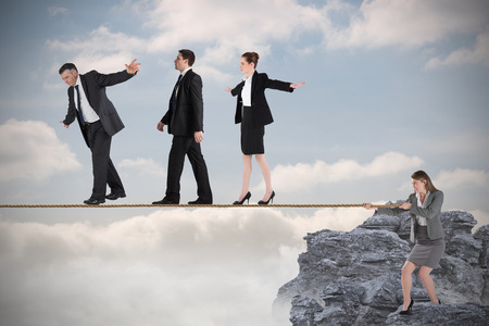 Young businesswoman pulling a tightrope for business people against rocky landscape photo