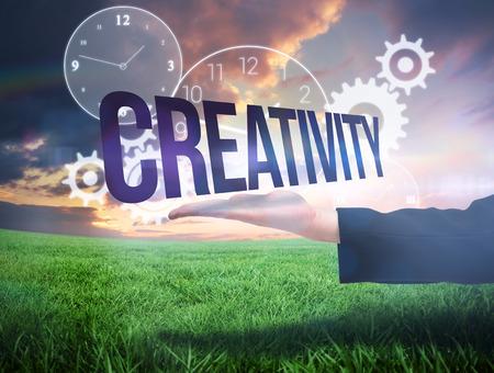 Businesswomans hand presenting the word creativity against green field under orange sky photo