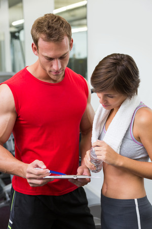 personal trainer: Handsome personal trainer with his client looking at clipboard at the gym