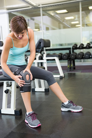 injured knee: Fit brunette sitting on bench holding injured knee at the gym