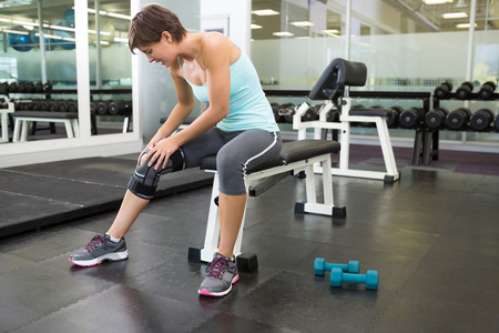 Fit brunette sitting on bench holding injured knee at the gym photo