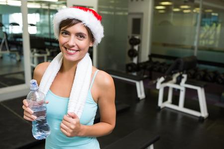 Fit morena no chapéu de Santa sorri na câmera no ginásio Imagens