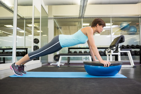 plank position: Fit brunette using bosu ball in plank position at the gym