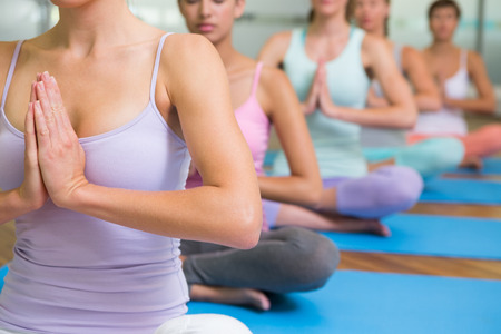 sport and leisure: Yoga class in lotus pose in fitness studio at the leisure center