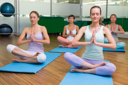 closed club: Smiling yoga class in lotus pose in fitness studio at the leisure center Stock Photo