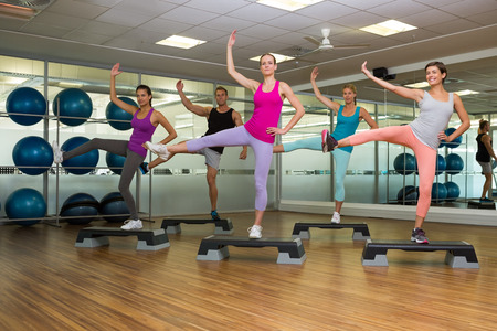 Fitness class doing step aerobics at the gym photo