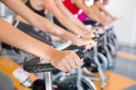 fitnes: Klasa wirowania pracuje w rzędzie na sali gimnastycznej