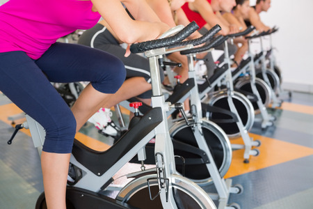 Clase de spinning que se resuelve en una fila en el gimnasio Foto de archivo - 30881163