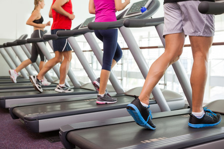 running man: Row of people on treadmills at the gym Stock Photo