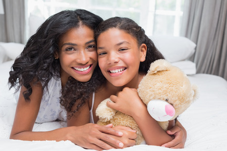 Pretty woman lying on bed with her daughter smiling at camera at home in bedroom photo
