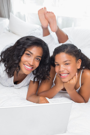 Smiling mother and daughter using laptop together on bed at home in bedroom photo