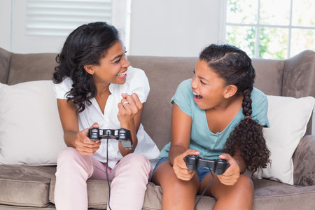 Happy mother and daughter playing video games together on sofa at home in living room photo