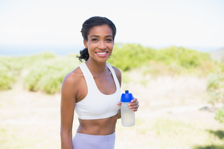 Fit woman holding sports bottle smiling at camera on a sunny\ day in the countryside