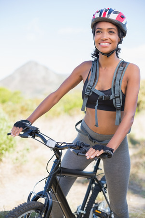 adventuring: Fit woman going for bike ride on a sunny day in the countryside